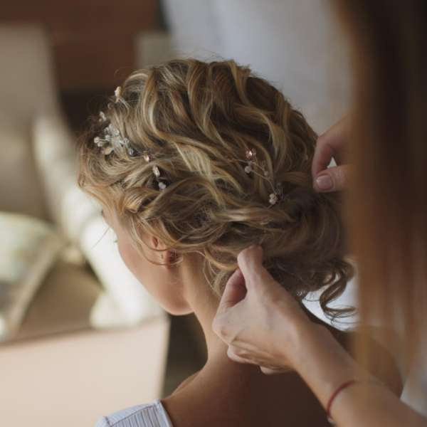 A bride getting hair styled from the back.