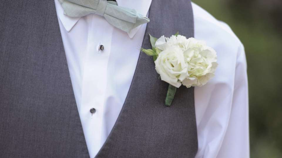 Beautiful white boutonniere on gray suit