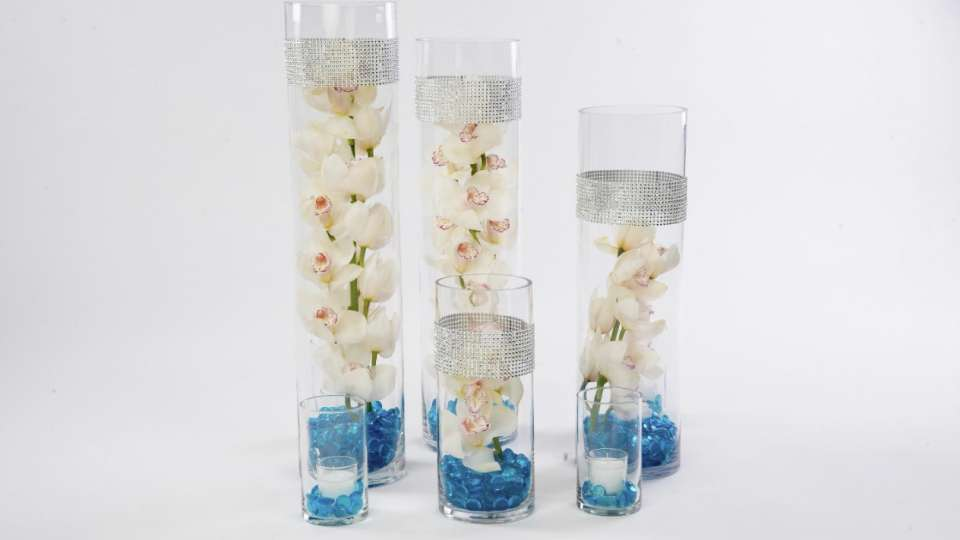 Complete your wedding decor with a triple floral centerpiece with blue vases and white flowers