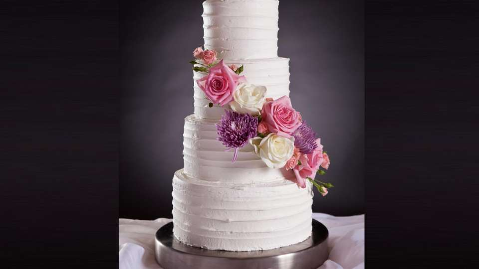 Mandalay Bay Wedding Cake with four layers and white pink and purple roses