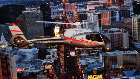 Image of a Maverick helicopter flying over the Strip at night during the Vegas Nights tour.