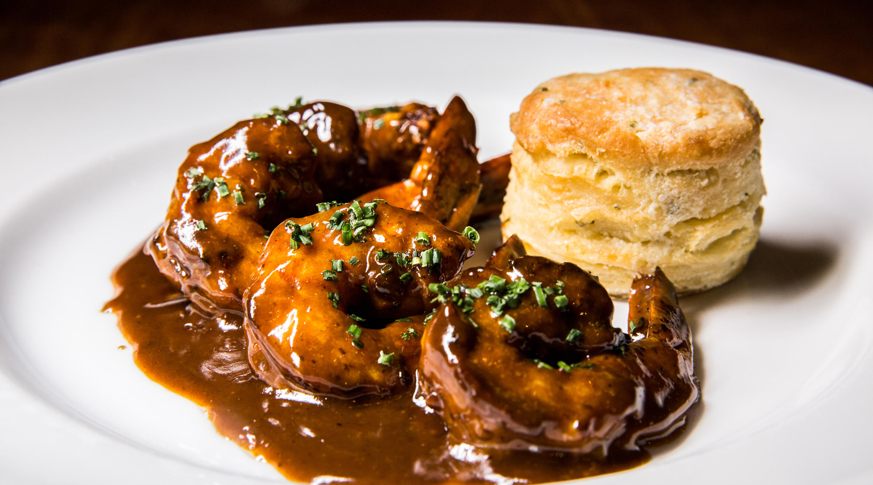 A plate of BBQ shrimp with a biscuit from Emeril's.