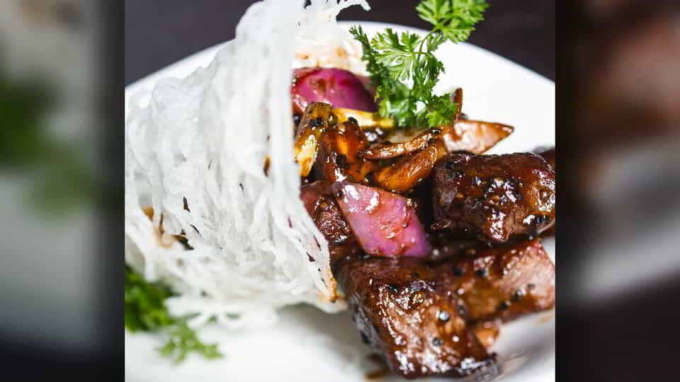 Signature dish stir fry black pepper rib eye beef with merlot