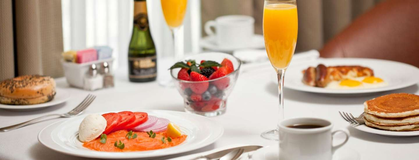 A breakfast featuring smoked salmon, pancakes, orange juice and champagne inside a room.