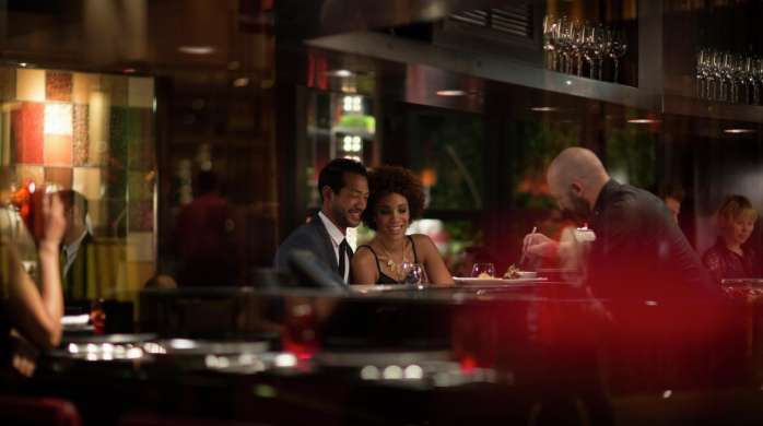 Couple eating and having fun at L'Atelier de Joel Robuchon.