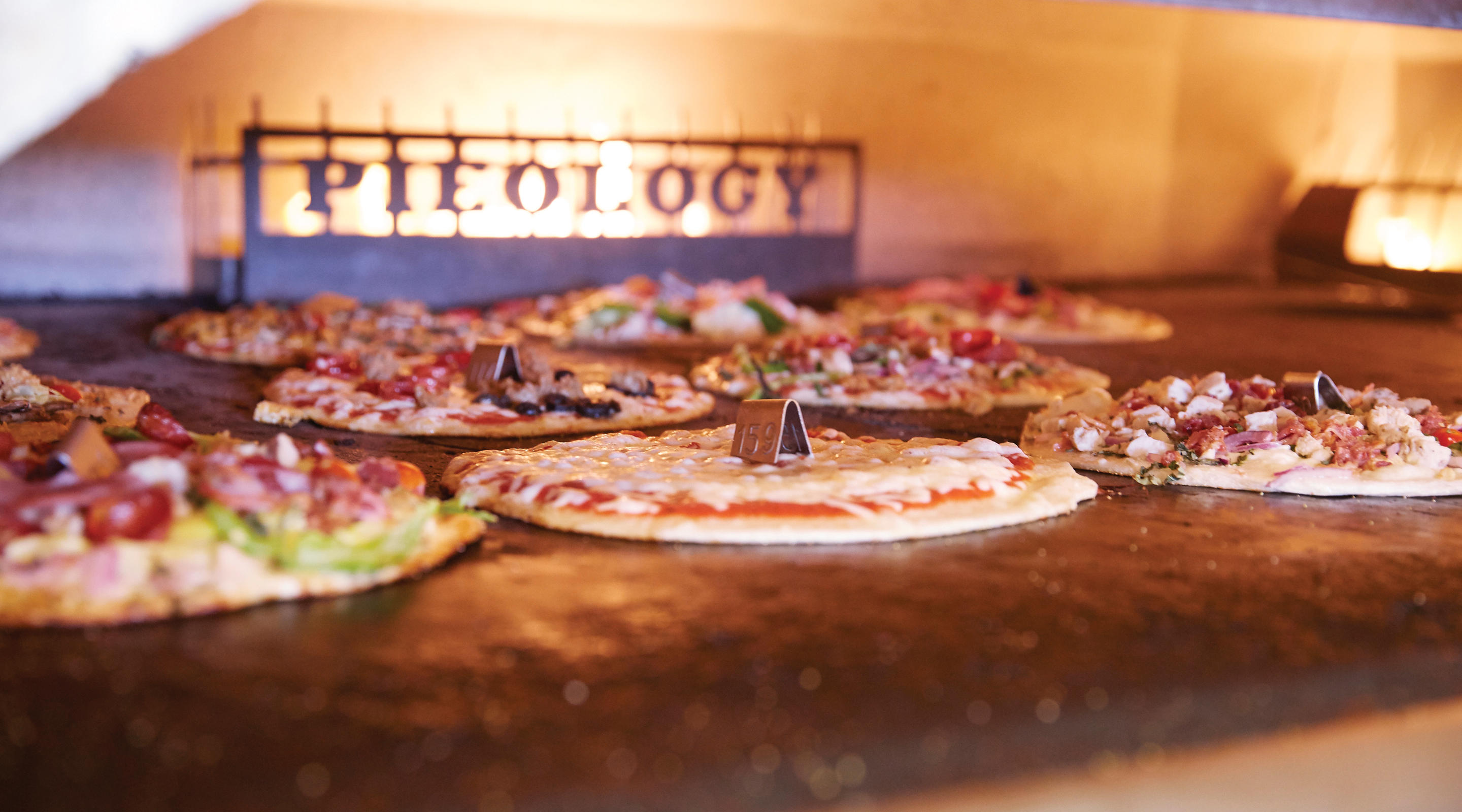 Pieology pizzas baking in oven
