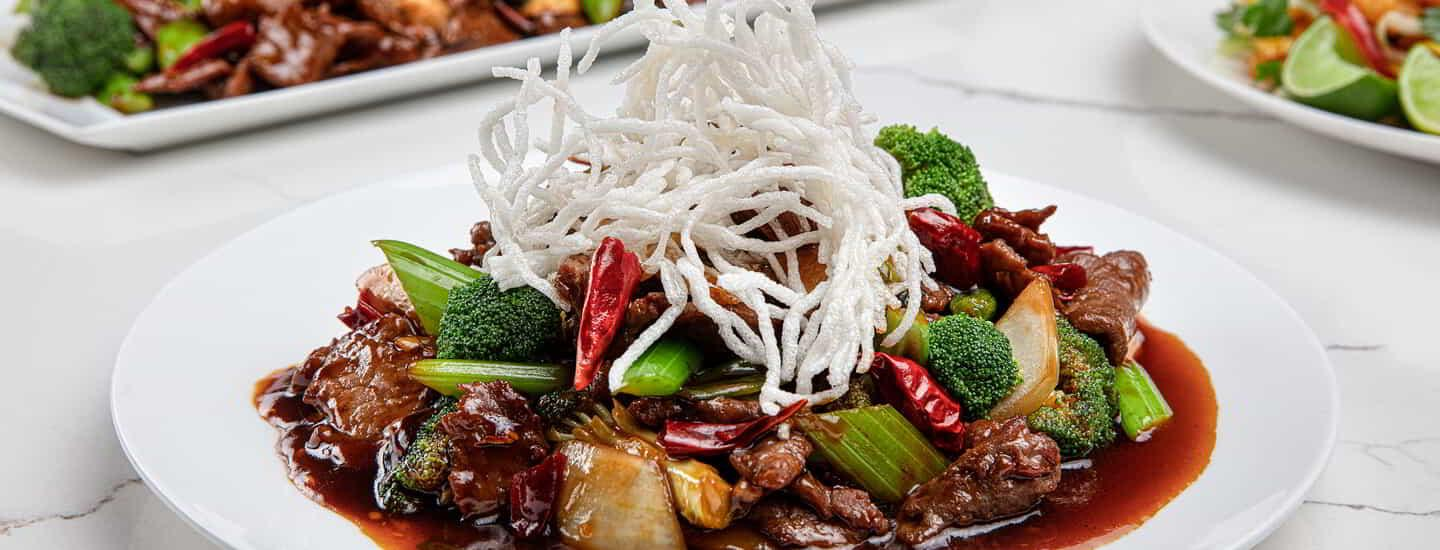 A plate of Mongolian Beef on a Grand Wok Noodle Bar table.