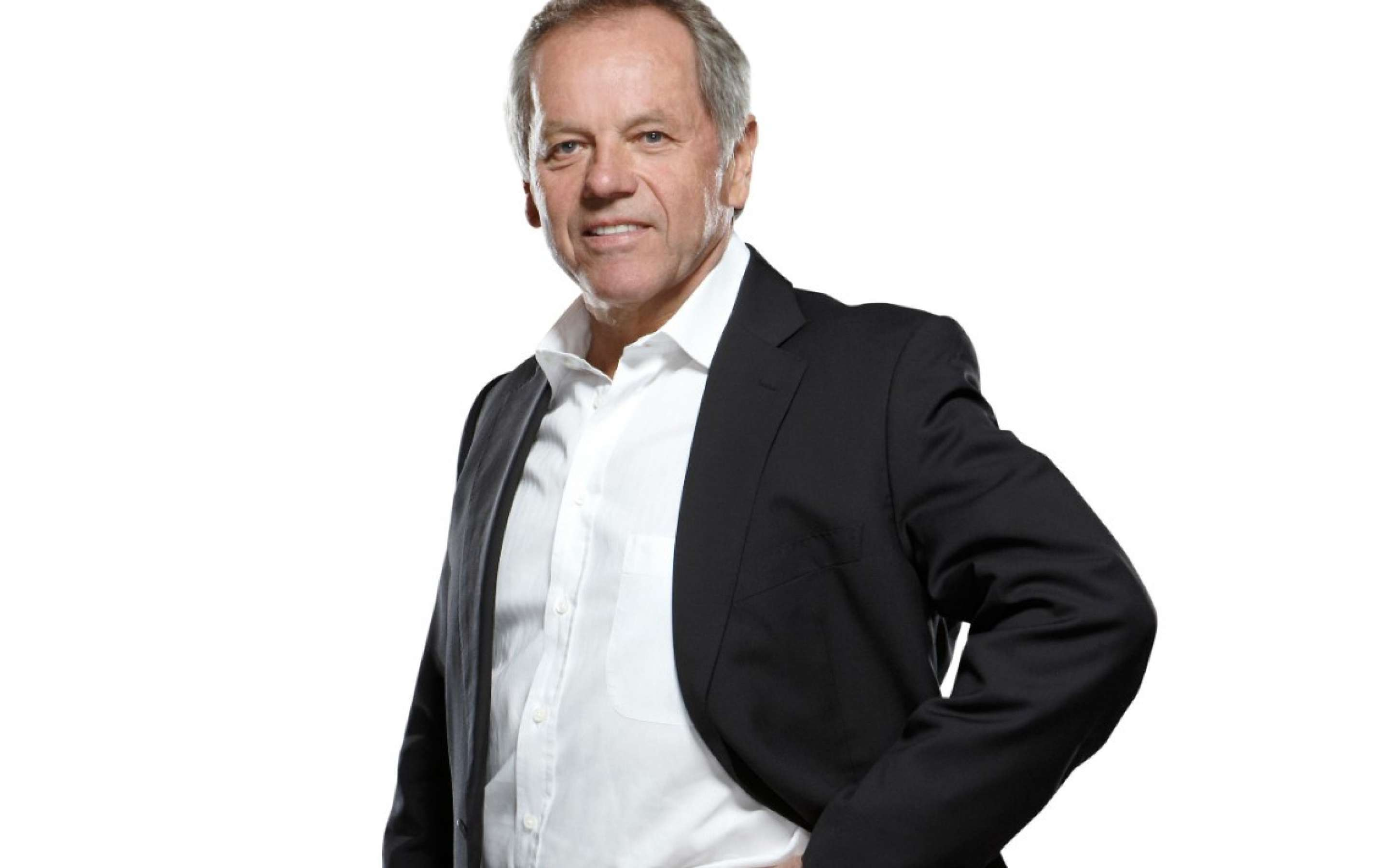 Chef Wolfgang Puck standing in a black suit