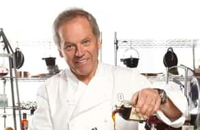 Photo of Wolfgang Puck smiling while cooking.