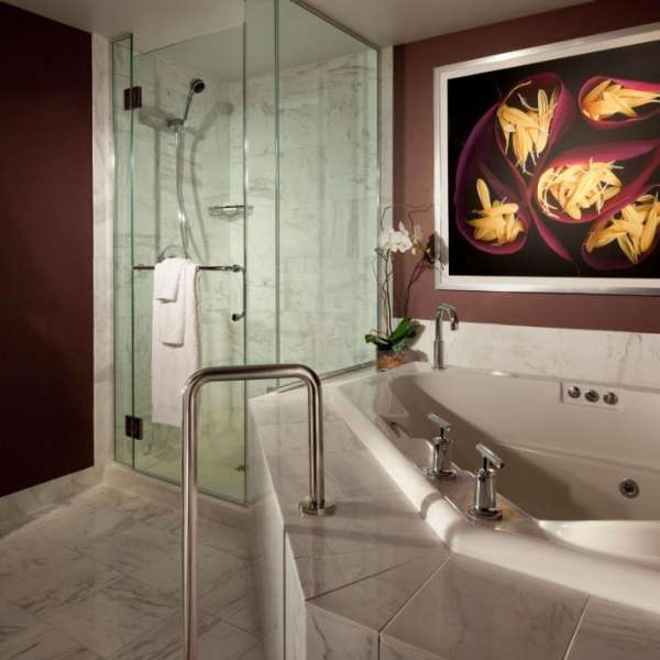 A whirlpool spa tub and separate shower in Carrera marble-adorned bathroom
