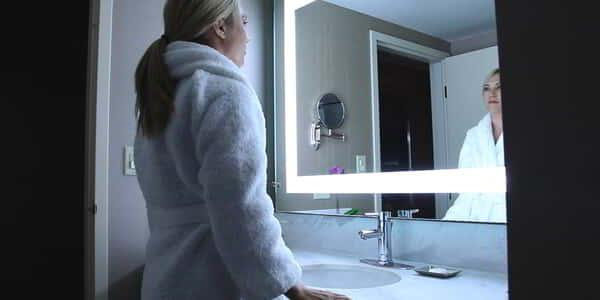 Woman standing in the bathroom with a robe on looking into the state-of-the-art light therapy mirror in one of the Stay Well rooms only available at MGM Grand