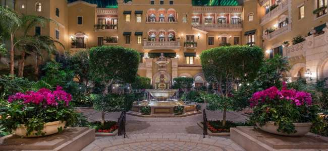 mgm-grand-hotel-rooms-mansion-exterior-atrium-night-light-water-fountain-hero-shot-@2x.jpg.image.650.300.high