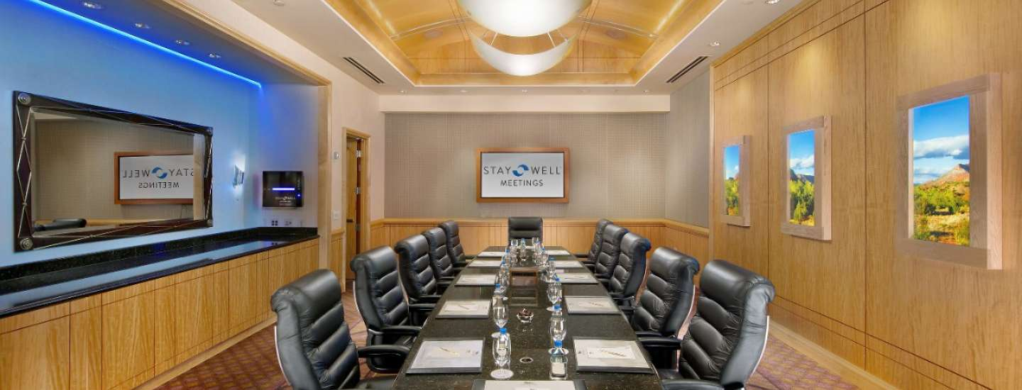 A Stay Well meeting room with the logo on the screen.
