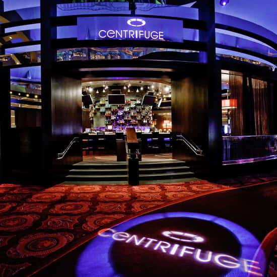 A wide view of the exterior of the Centrifuge with the logo lit up on the floor.