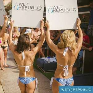 Wet Republic Servers Holding Up Signs in Their Bikinis