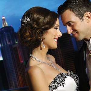 Bride and Groom outside on the balcony of the Skyline Terrace Suite with a view of the strip and the MGM Grand Marquee Sign at MGM Grand