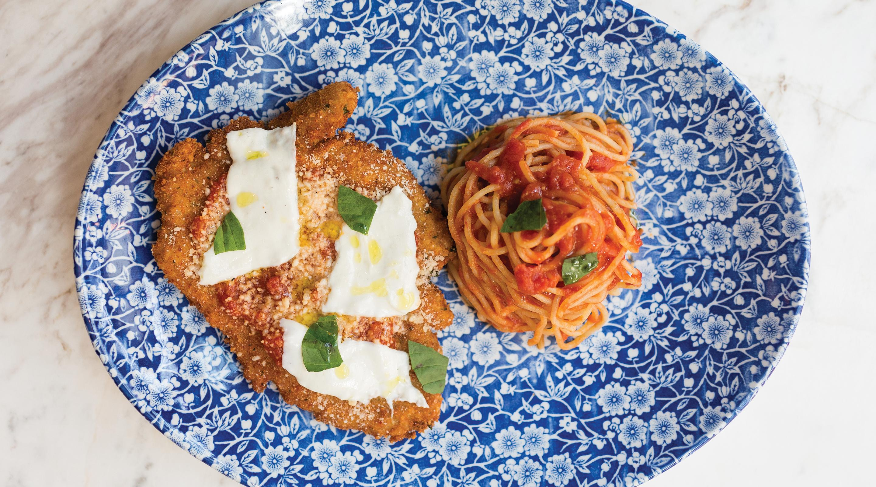 A plate of chicken parmesan and spaghetti with sauce.