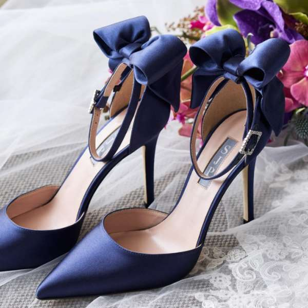 Pair of blue heels next to flower bouquet.
