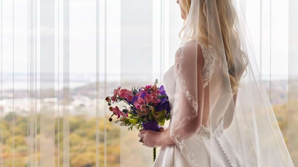 Bride holding flowers by a window.
