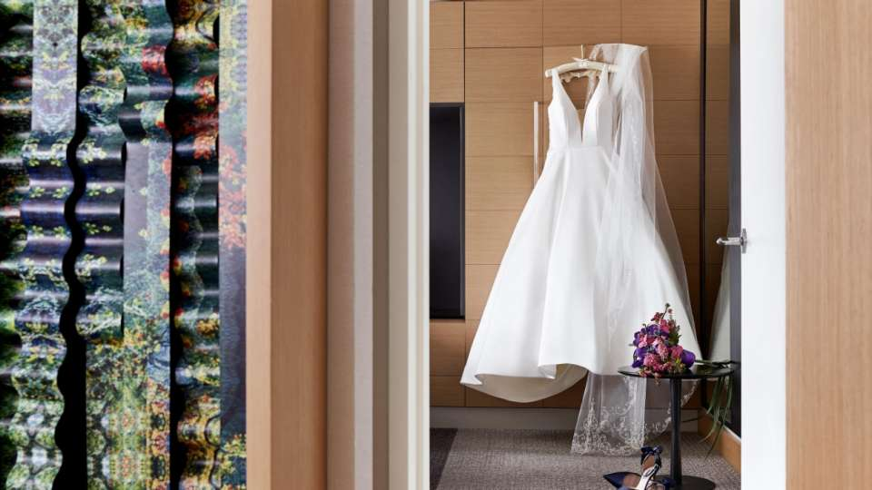 A wedding gown hung on the wall.