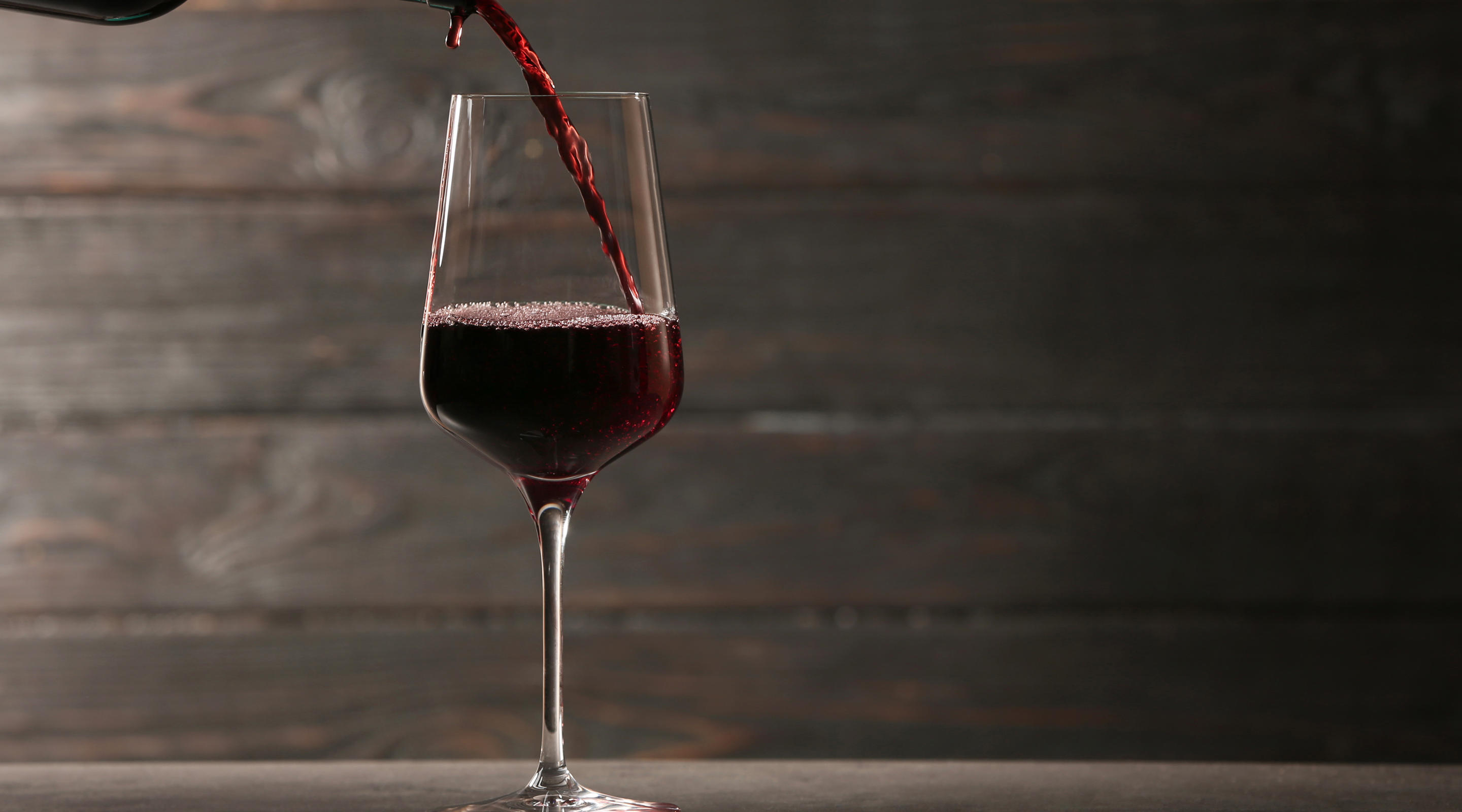 A glass of red wine pouring.