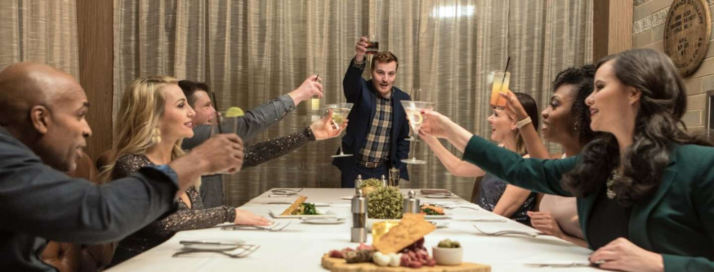 Friends celebrate at the dinner table with a group toast.