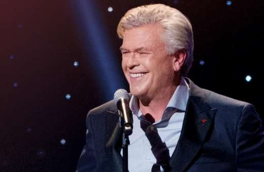 Ron White smiles on stage while performing.