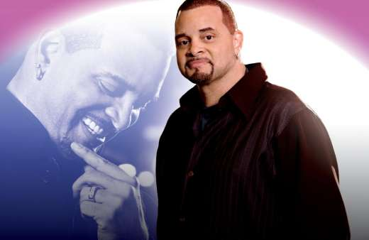 Sinbad poses in front of a silhouette photo of himself.