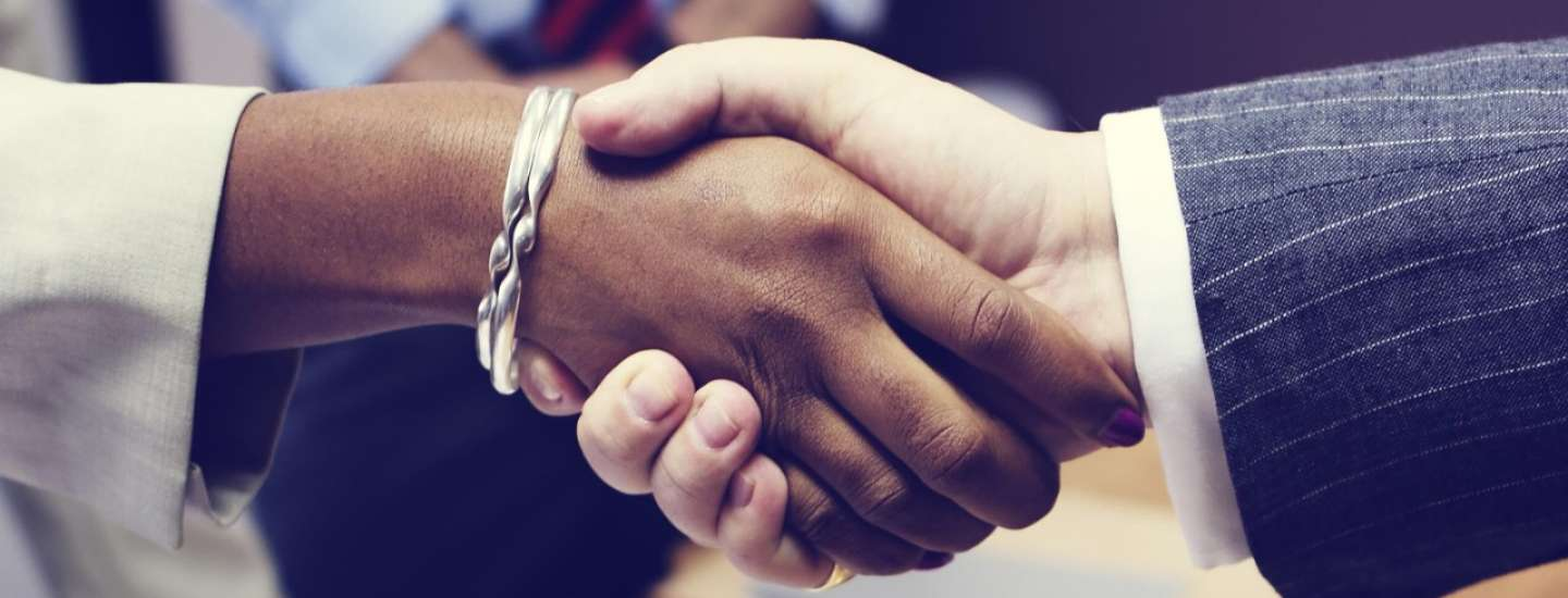 A male and female shake hands on a business deal.