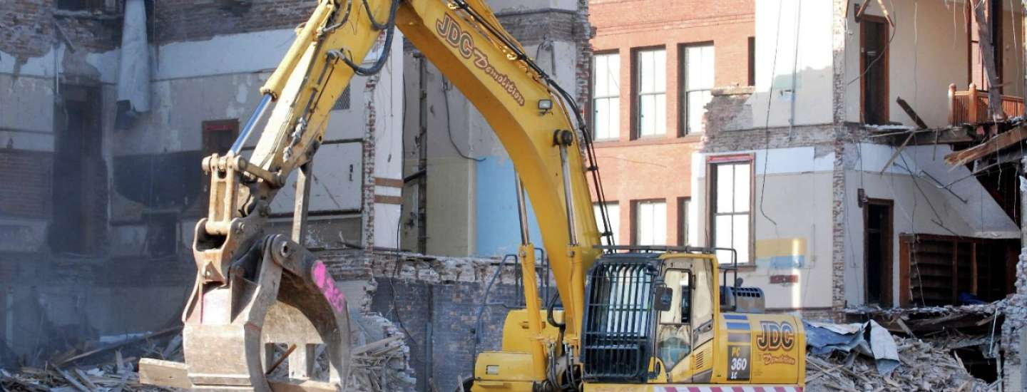 Excavator is removing debris from a knocked down building.