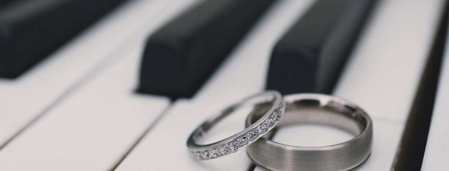 His and Hers wedding rings lay together on a white piano key.