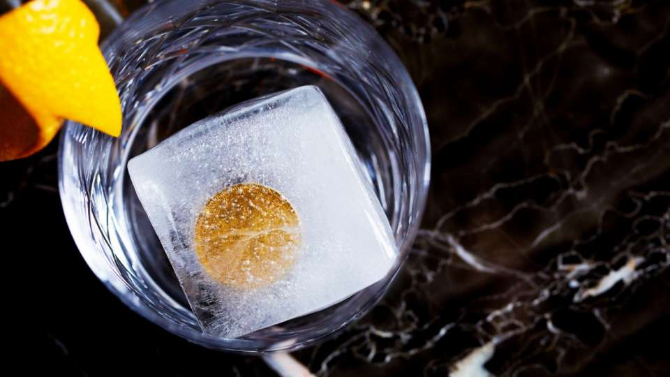 A gold coin sits frozen in an ice cube.
