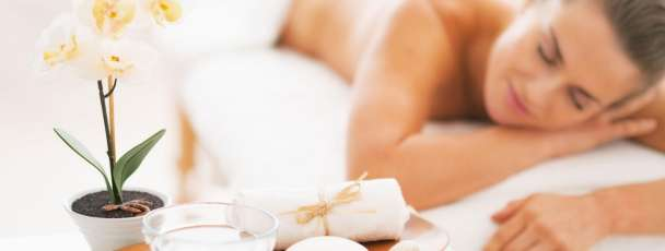 Closeup on spa therapy ingredients and young woman in background
