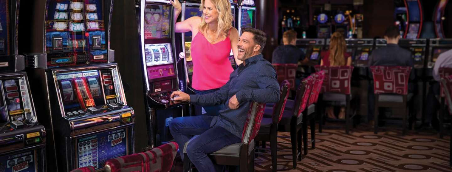 Couple playing slot machine.