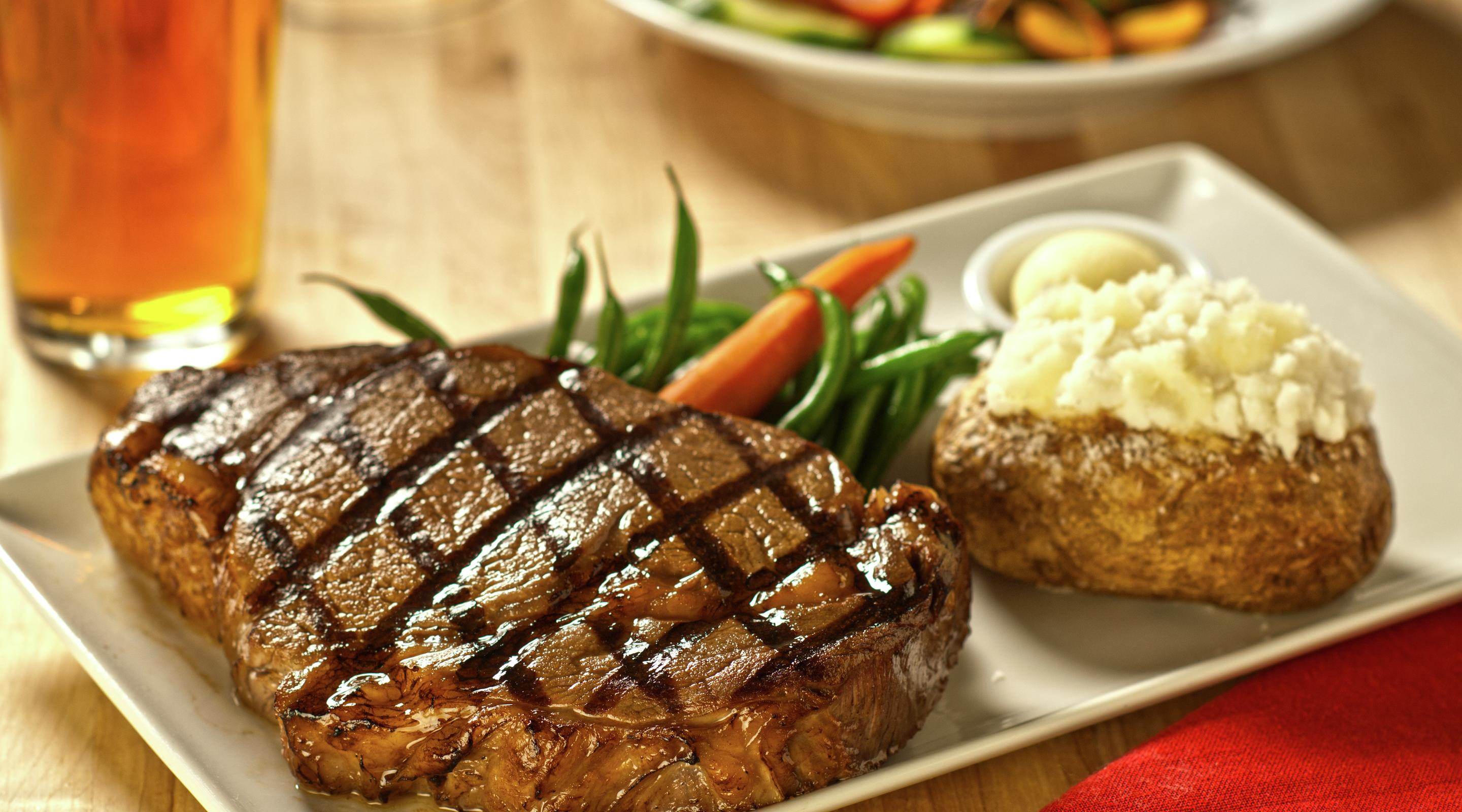Ribeye steak paired with a baked potato and vegetables.