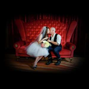 Zumanity Wedding couple sitting and kissing each other on love seat.