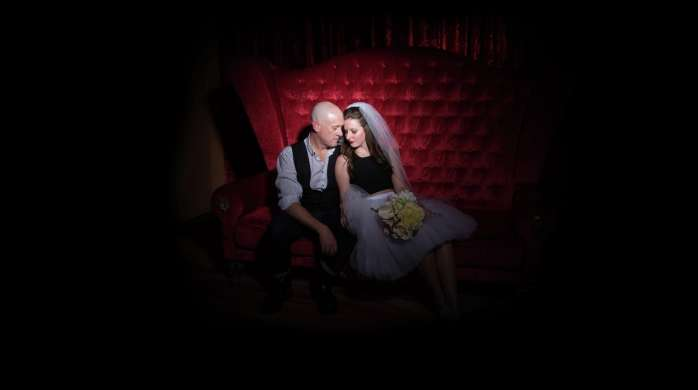 Zumanity Wedding with a couple sitting on love seat.