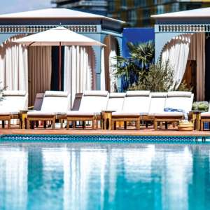 NoMad Las Vegas pool with lounge chairs and cabanas behind it.