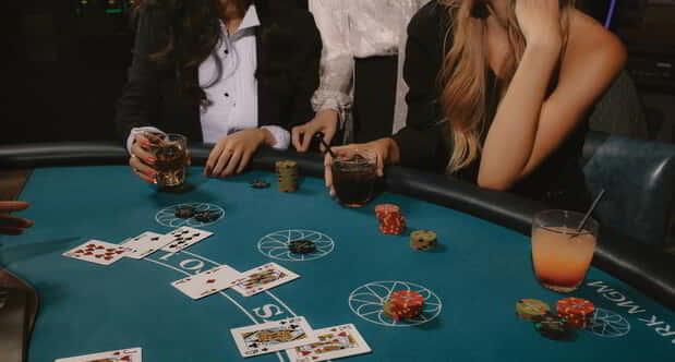 Group of people playing blackjack at the casino.