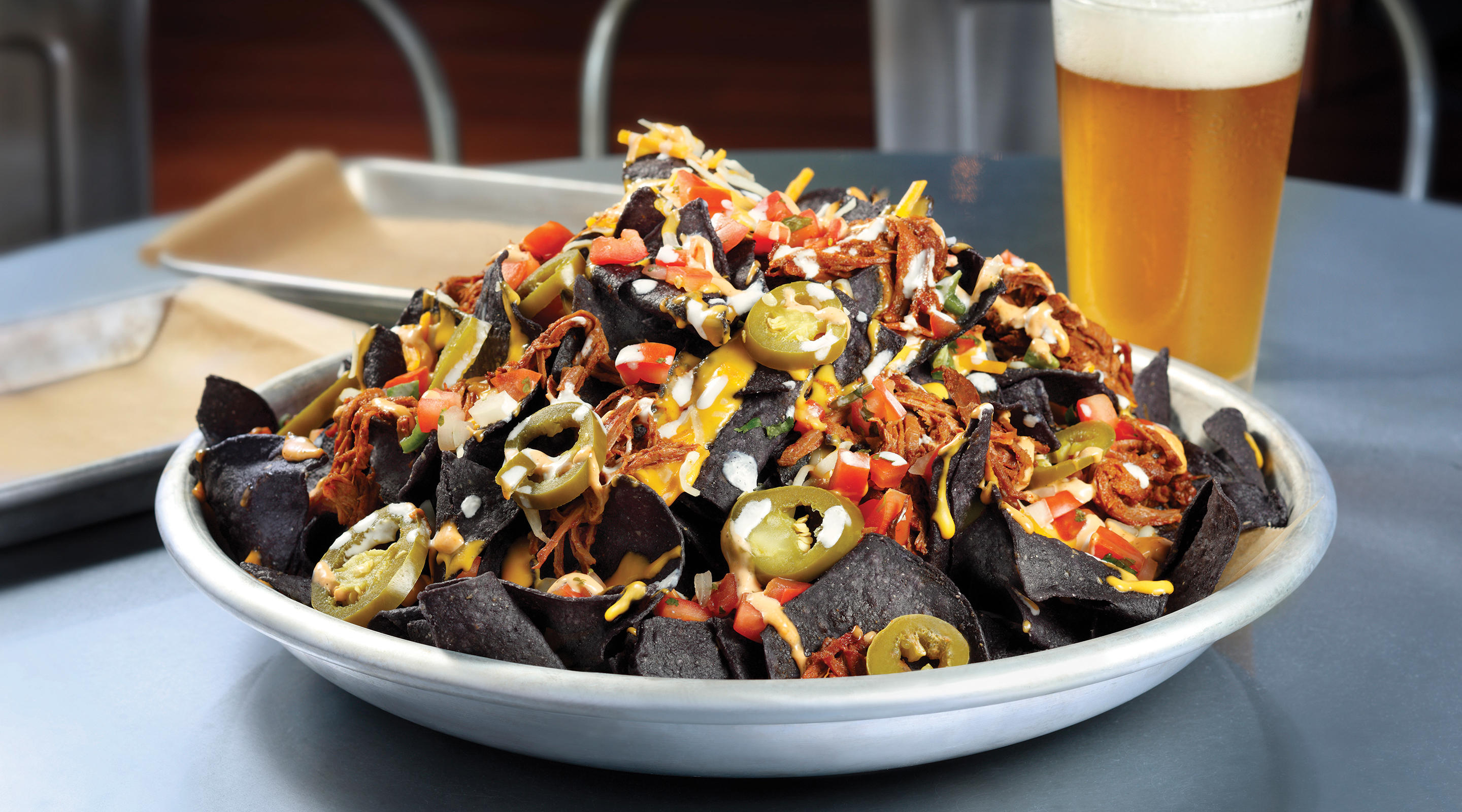 A plate full of barbacoa beef nachos sits on a table next to a cold beer.