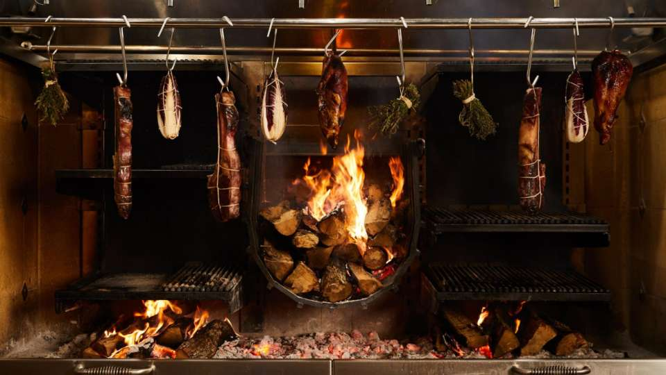 Prime selections of meat cooking over an open fire at Manzo.
