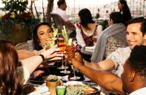 A group of people toasting on the patio at Primrose.