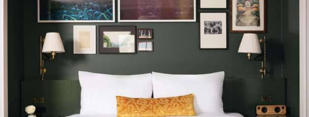Nighthawk Suite king bed with art collection on the wall above it.