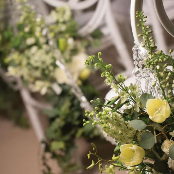 Flower arrangements attached to chairs for a wedding.