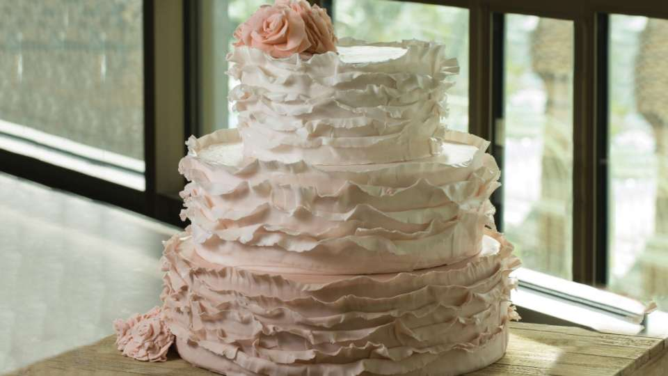 Tiered wedding cake with ruffled icing.