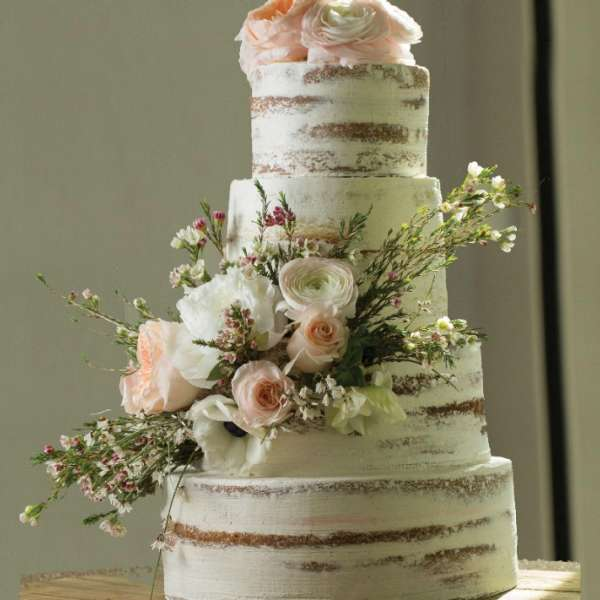 Rustic themed tiered wedding cake with flowers.
