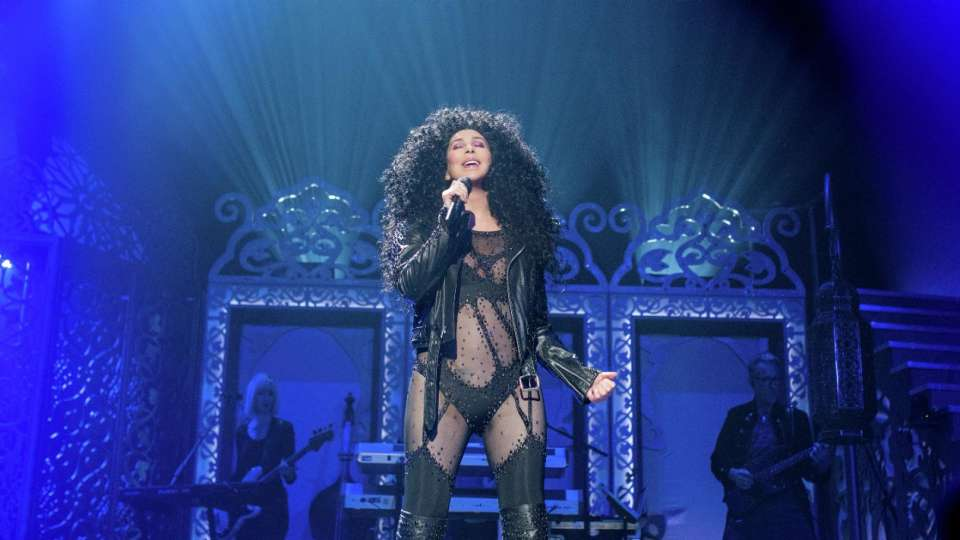 Cher performing solo with black outfit and blue background.