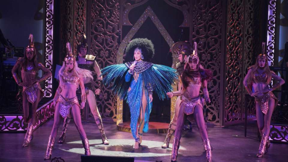 Cher performing with blue feather outfit.