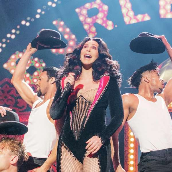 Cher performing with male dancers with burlesque background.