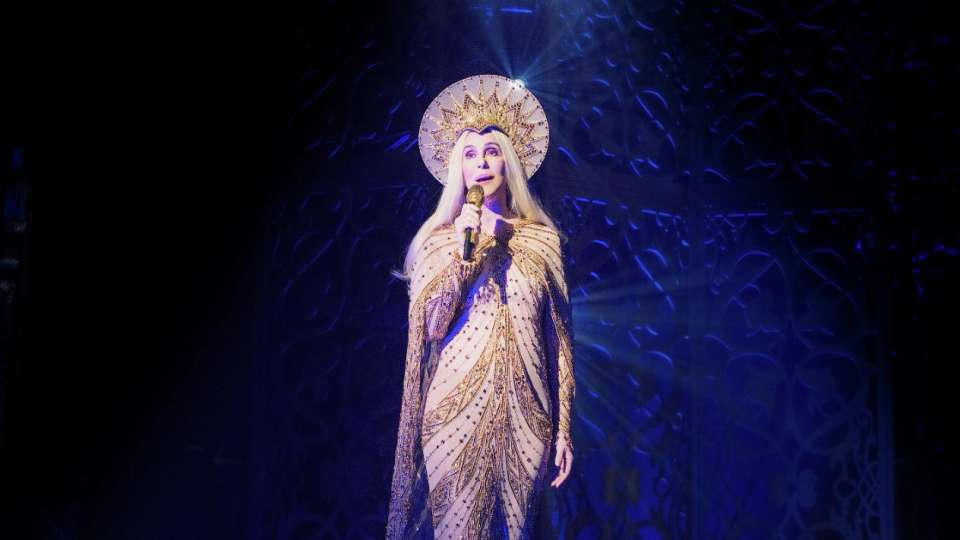 Cher performing solo with gold gem outfit.